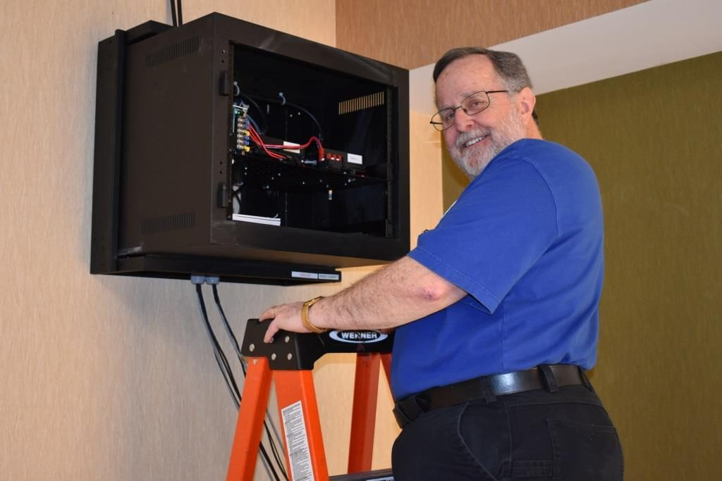Paul, N3RQV, is standing on a stepladder next to the wall-mounted radio cabinet. The power supply and TM-D710 radios can be seen inside the cabinet.